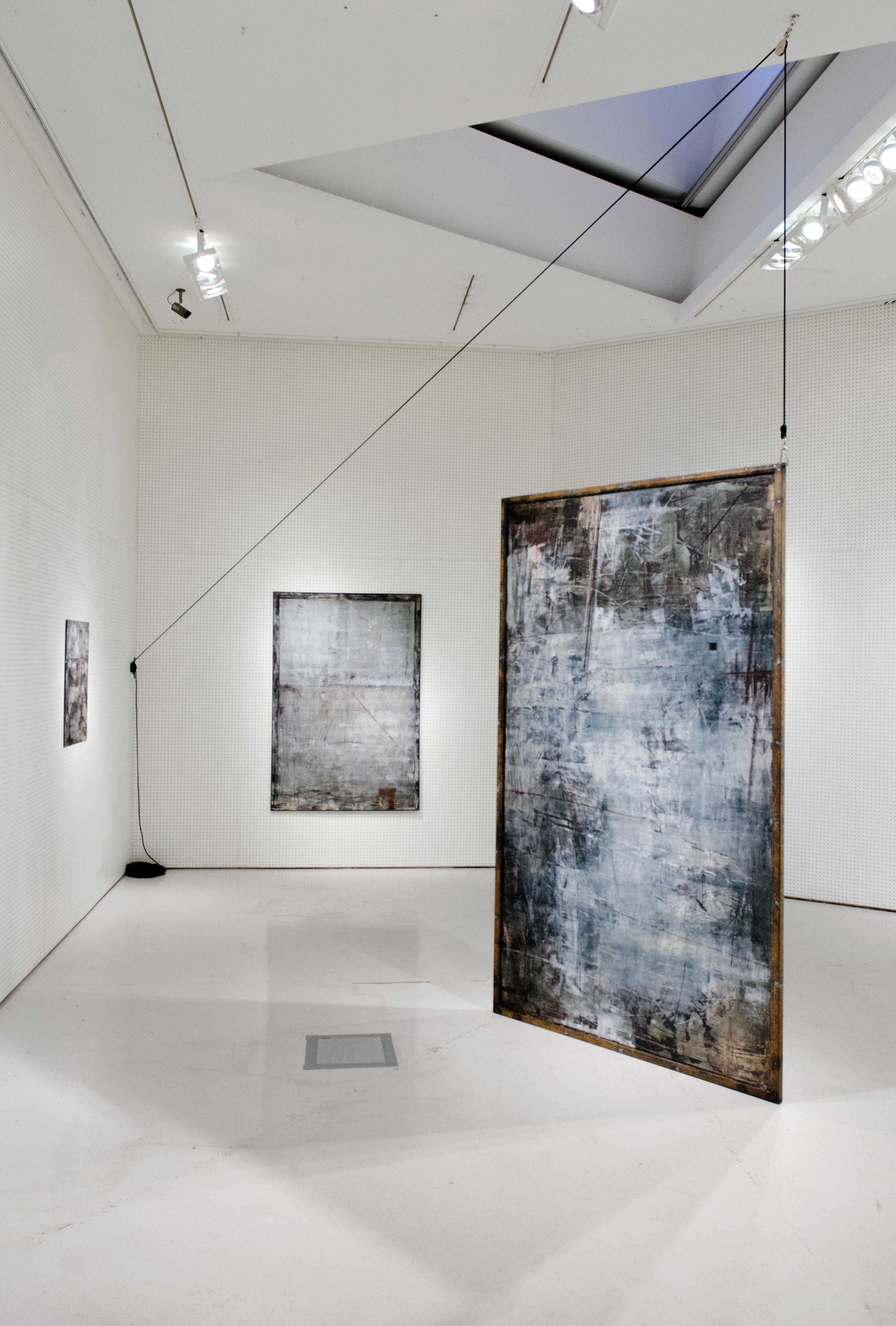 Kolme tekstuurista mustavalkomaalausta ripustettu galleriatilaan.