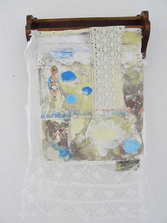 Pienessä hyllyssä roikkuva kankainen kollaasi. Valkoista pitsia, pieni naisen kuva. Harmaata, sinistä, keltaista ja valkoista maalausjälkeä.