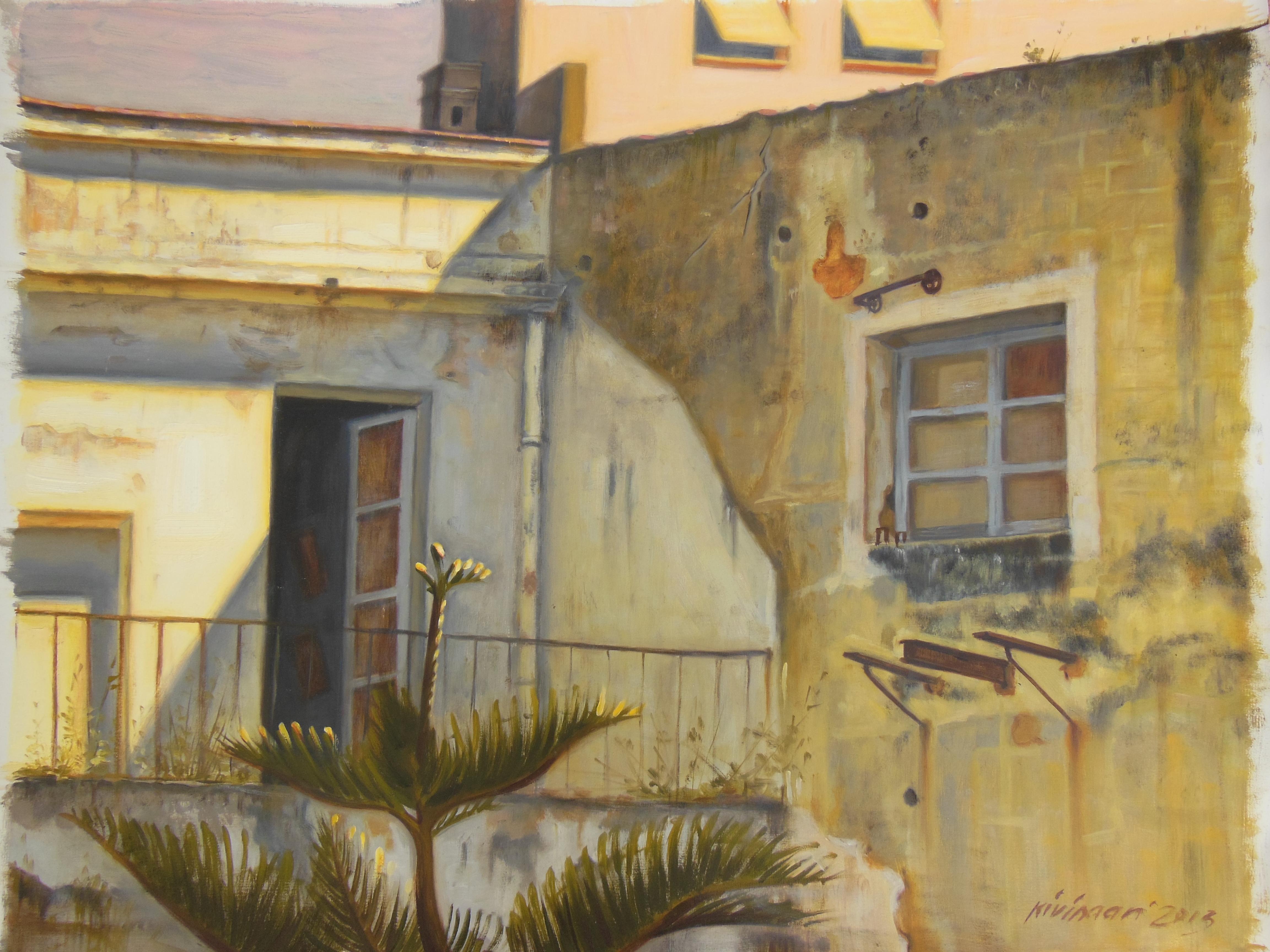 Kellertävä rauniotalo, avoin ovi, kaide, ikkuna. Etualalla palmu.