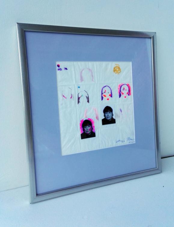 Seinää vasten nojaavat kehykset, joiden sisällä pieniä kasvoja sisältävä kuva.