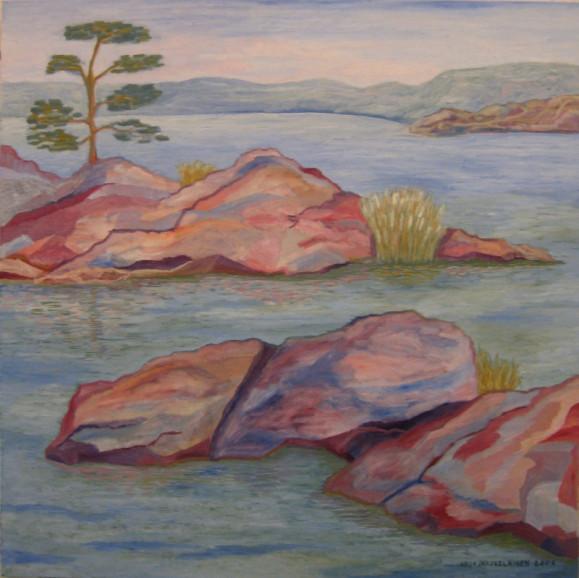 Kirjavaa rantakalliota, yksi puu, heinää. Horisontissa kumpuileva vastaranta, vaalea taivas.