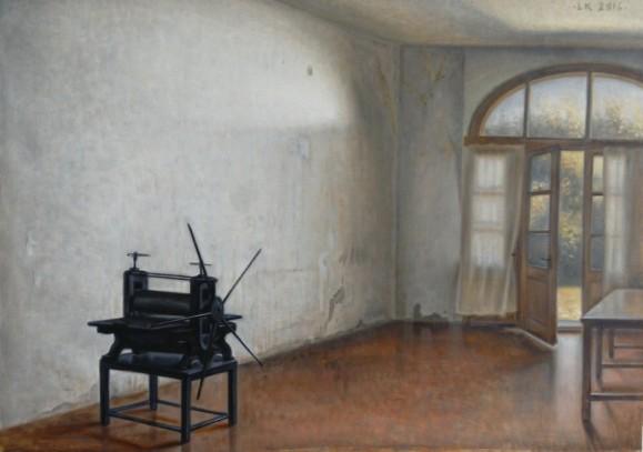 Huoneessa musta grafiikan prässi ja pöytä, suuri ikkuna josta näkyy puita, valkoiset verhot. Ruskea lattia, valkoiset seinät.