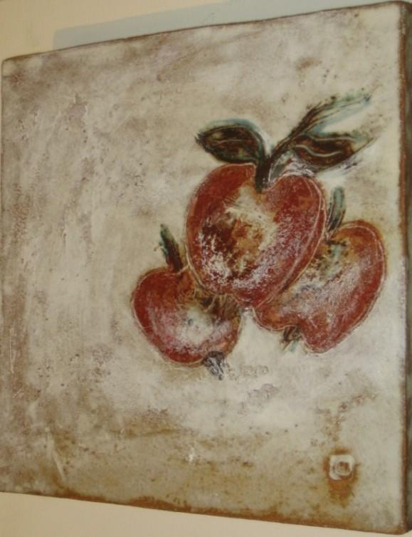Kolme rosoisen punaista omenaa valkoisella rusehtavalla taustalla.