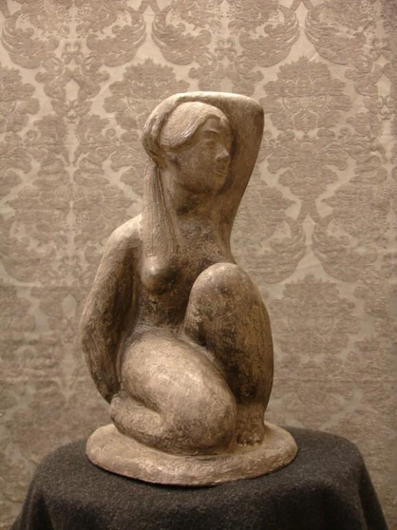 Rusehtava kyykistynyt tyttö, taustalla koristeellinen vaaleanruskea tapetti.