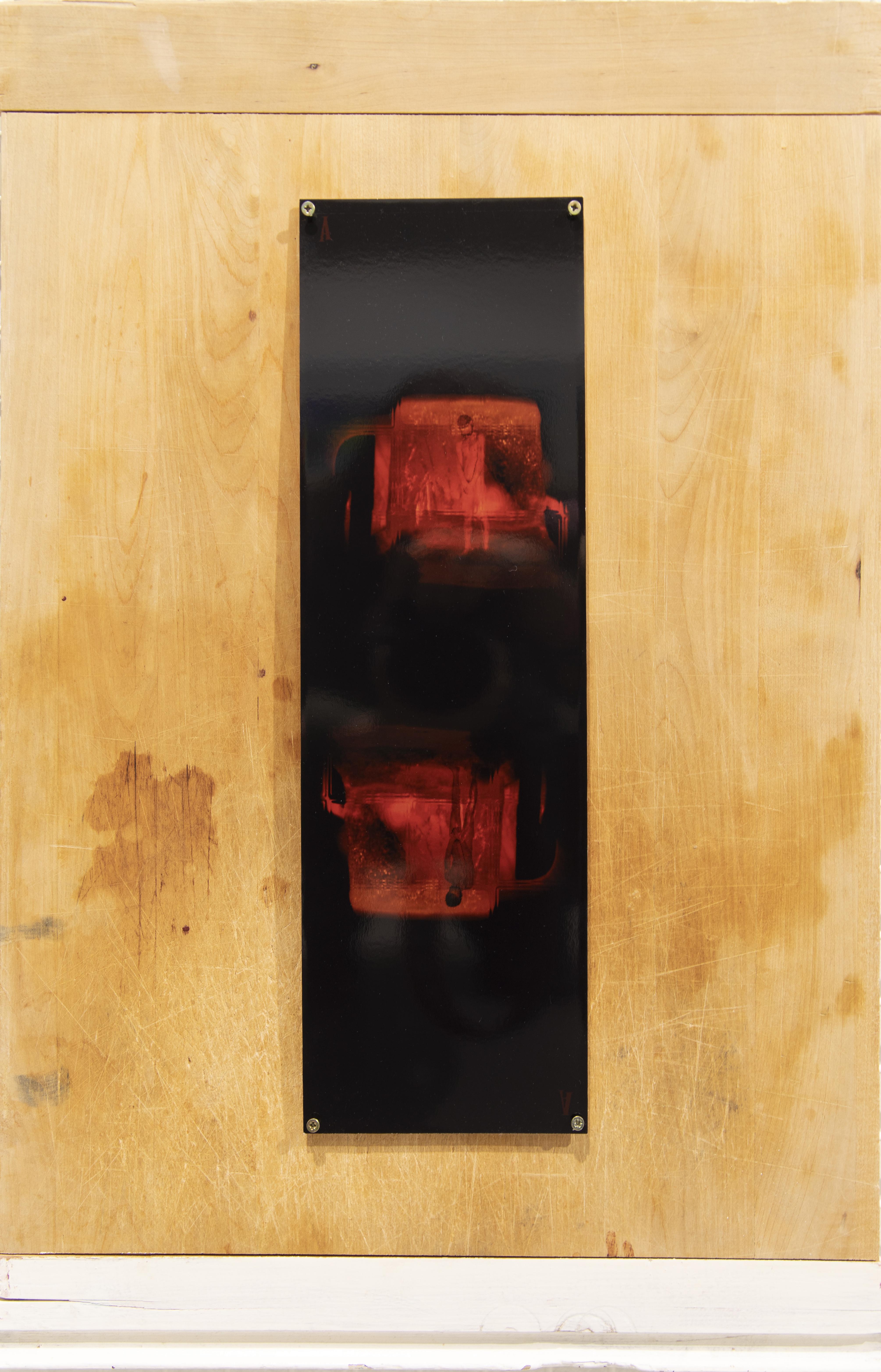Puulevylle ruuveilla kiinnitetty musta valokuva, jossa kaksi kertaa toistuva mies punaisessa valossa.