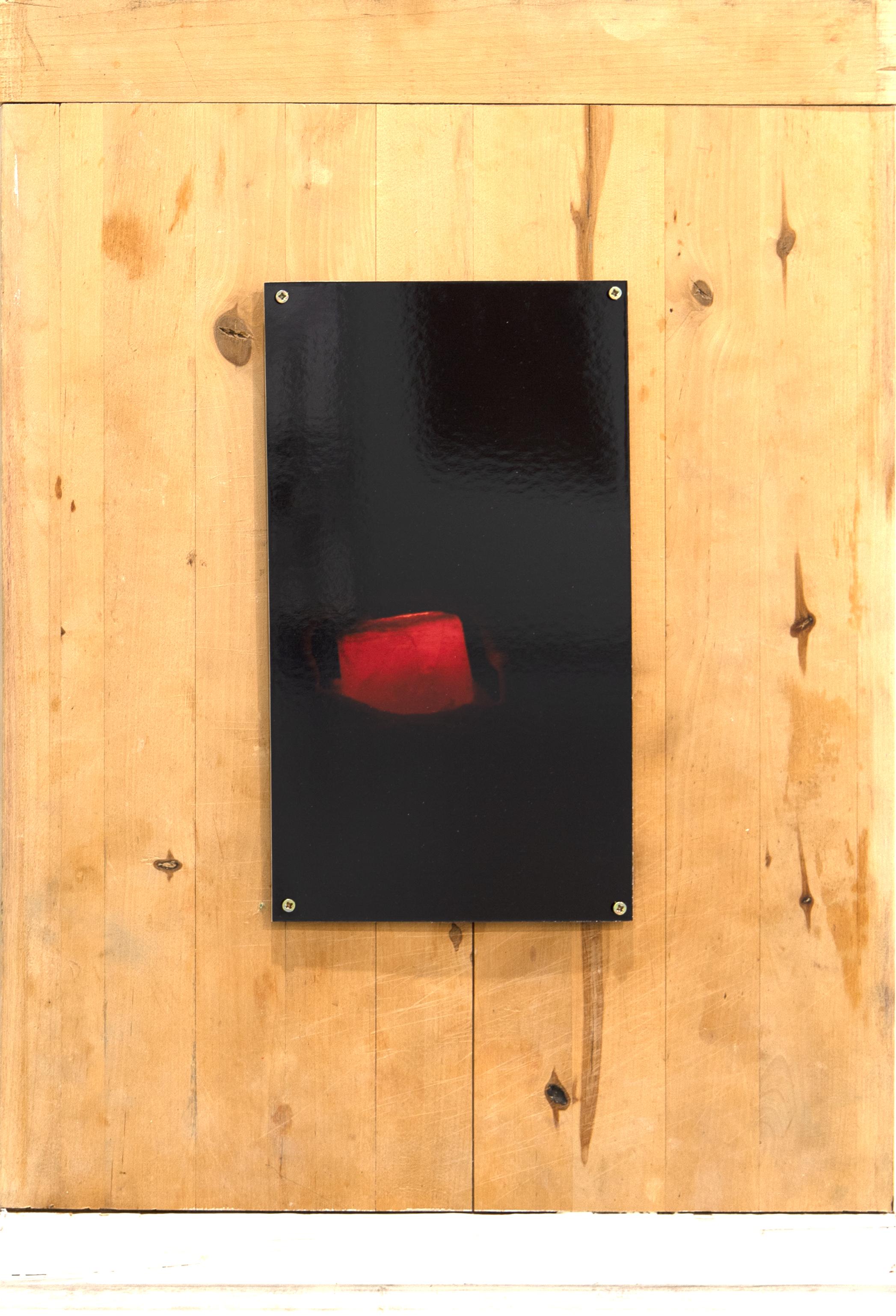 Puulevylle ruuveilla kiinnitetty musta valokuva, jossa epämääräinen punainen objekti.