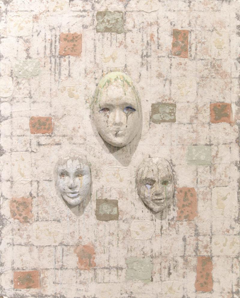 Kolme kohoavaa kasvoa, tekstuurinen tausta jolla tiilimäistä kuviota. Siellä täällä tiilin värisiä ja ruskeita kulmioita.