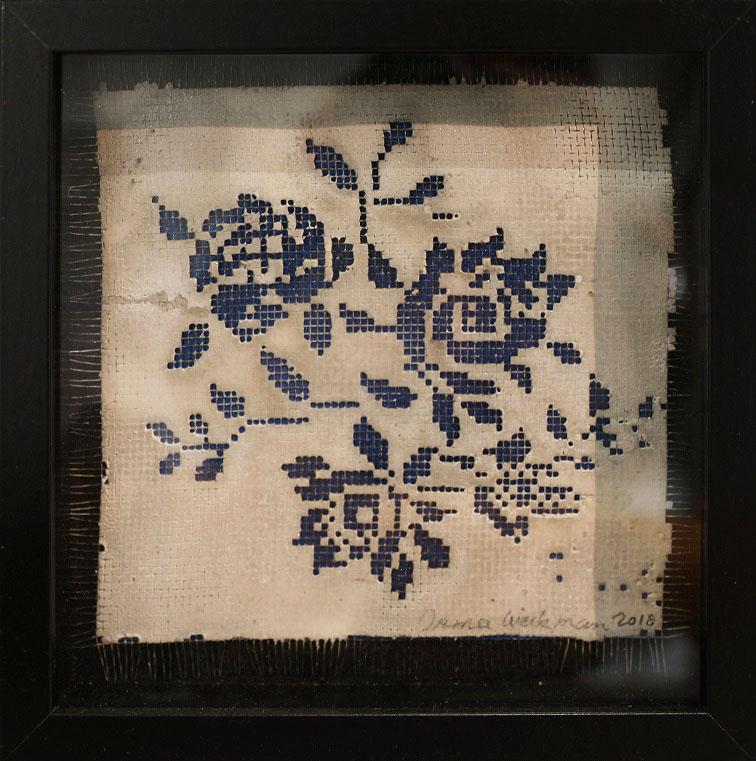 Ristipistoa muistuttavia sinisiä ruusuja valkoisella. Musta kehys.