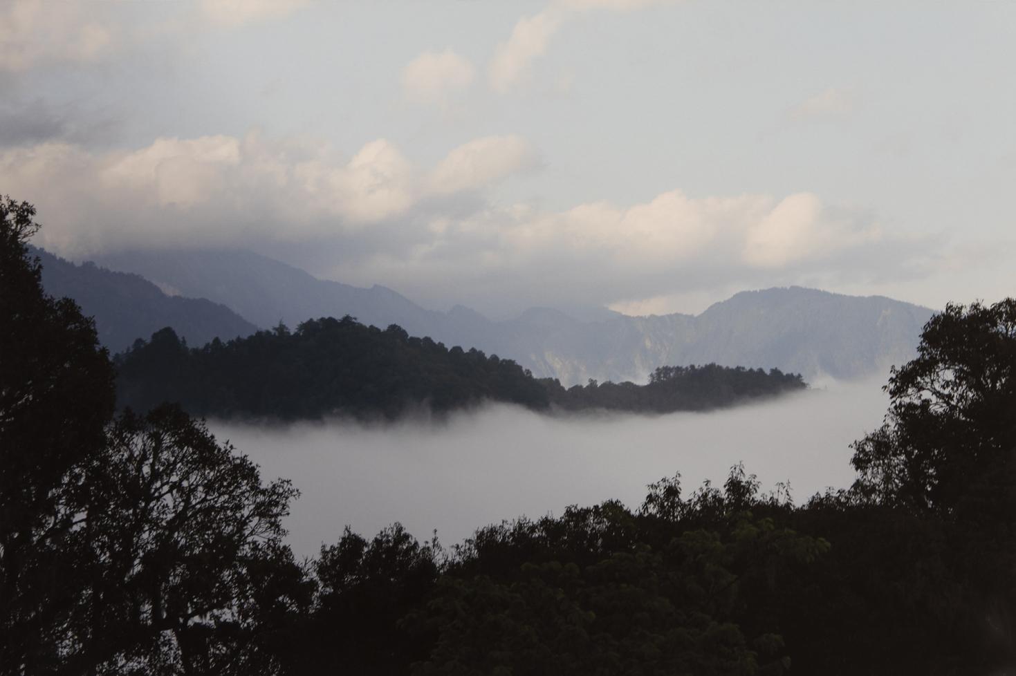 Kuulas maisema: puolipilvinen taivas, vuoria, metsää, usvainen laakso.