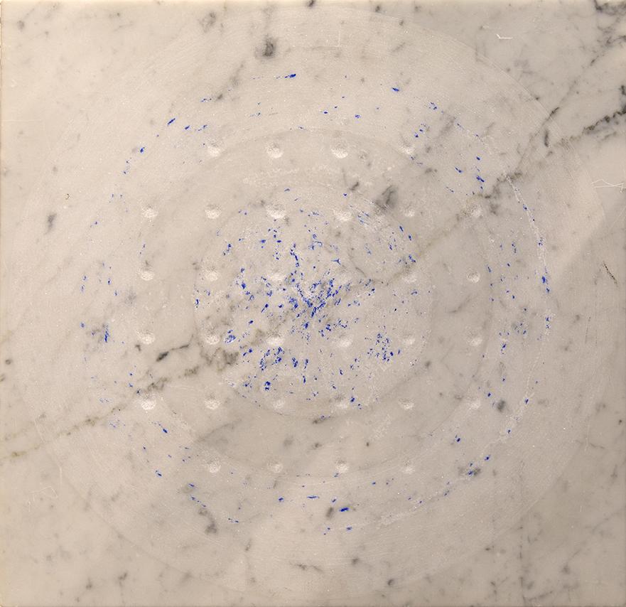 Kaiverrettu ympyrä ja sinisiä jälkiä marmorilla.