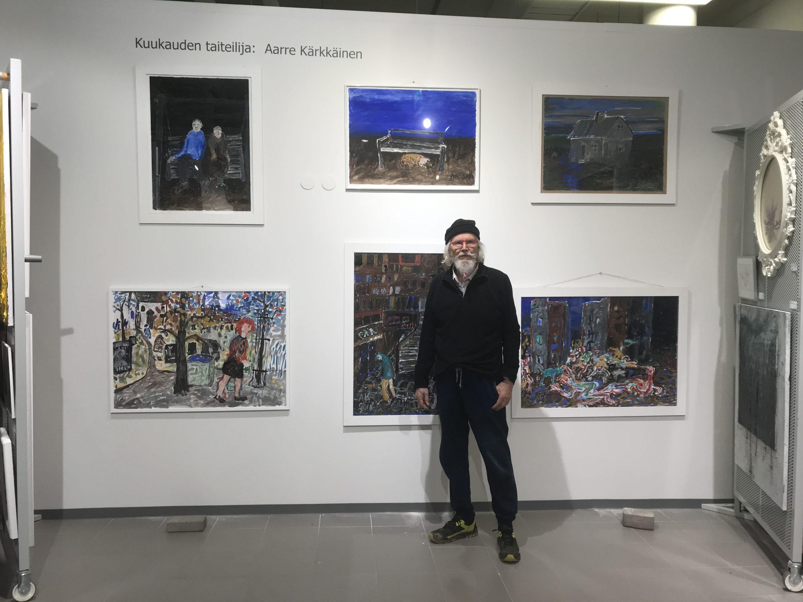 Taiteilija poseeraa seinälle ripustettujen teostensa edessä.
