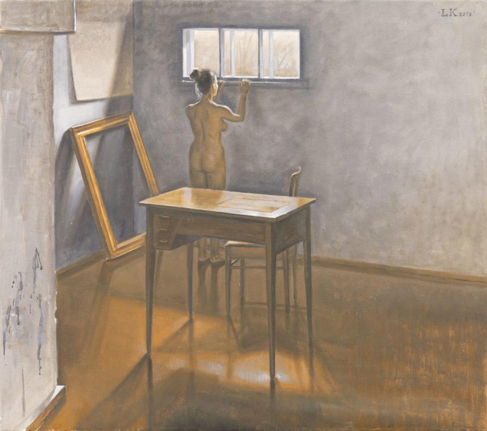 Huone, jossa on valkoiset seinät ja ruskea lattia. Keskellä työpöytä ja tuoli. Seinää vasten tyhjä kehys. Alaston nainen katsoo ulos ikkunasta.