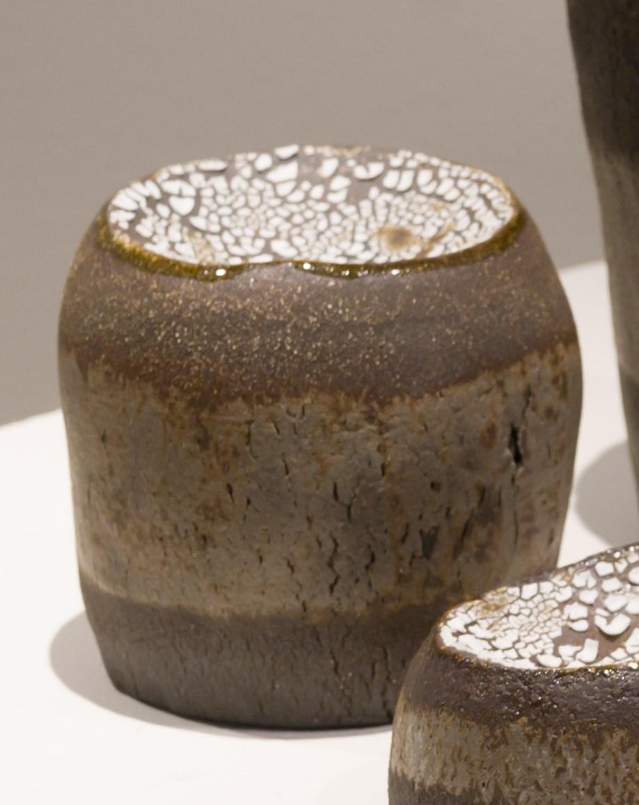 Kuivuuden alla on keraaminen koriste-esine tasolle kuten pöydälle tai hyllylle. Teos on tumman ruskea ja siinä on harmahtava raita, joka on tehty lasitteella. Hieman maljamainen pääliosa on lasitettu valkoisella ratkeilevalla lasitteella. Teos on käsinrakennettua kivitavaraa ja on ontto sisältä. Teoksen halkaisija vaihtelee ja on noin 11 cm. Korkeus on noin 15 cm.