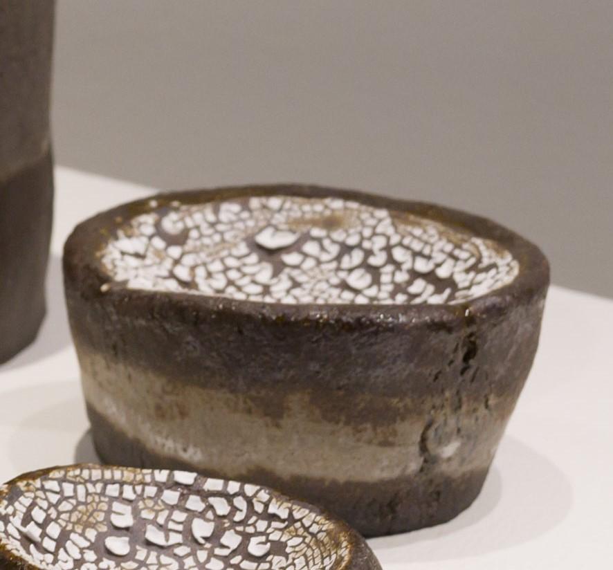 Kuivuuden alla on keraaminen koriste-esine tasolle kuten pöydälle tai hyllylle. Teos on tumman ruskea ja siinä on harmahtava raita, joka on tehty lasitteella. Hieman maljamainen pääliosa on lasitettu valkoisella ratkeilevalla lasitteella. Teos on käsinrakennettua kivitavaraa ja on ontto sisältä. Teoksen halkaisija vaihtelee ja on noin 12 cm. Korkeus on noin 6 cm.